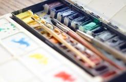Las pinturas de la acuarela en cubetas están en una caja plegable fotos de archivo libres de regalías