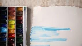 Las pinturas del artista con las pinturas de la acuarela en una hoja de papel Manos con un cepillo en el marco almacen de metraje de vídeo