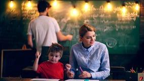 Las pinturas del muchacho en una sala de clase con un profesor Aprendizaje de concepto Alumnos en uniforme Profesor en sala de cl almacen de video