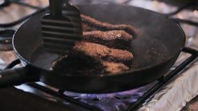 Las pinzas de las vueltas de los filetes del cocinero almacen de video
