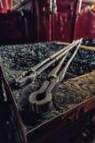 Las pinzas del hierro de un herrero mienten en un lugar del fuego Foto de archivo libre de regalías