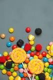 Las piruletas coloridas, los bastones de caramelo y los caramelos dulces se mezclan en fondo de madera gris imágenes de archivo libres de regalías