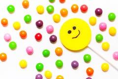 Las piruletas, sonrisa del caramelo encendido, se dispersan alrededor del jel colorido Foto de archivo