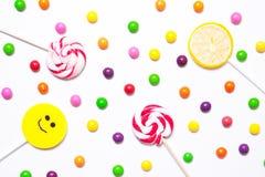 Las piruletas, sonrisa del caramelo encendido, se dispersan alrededor del jel colorido Imagen de archivo