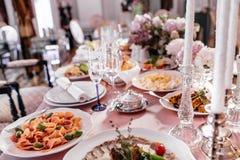 Las placas con el soporte del pan entre la cristalería chispeante en la tabla sirven Foto de archivo libre de regalías