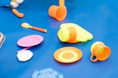 Las placas, las cucharas y las tazas, juguetes dispersaron en un azul Fotografía de archivo libre de regalías