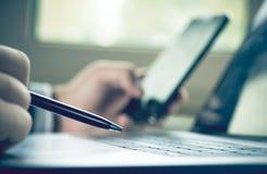 Las plumas del foco selectivo se sostienen a disposición en el teclado y el hombre de negocios del ordenador portátil del fondo u Imagen de archivo libre de regalías
