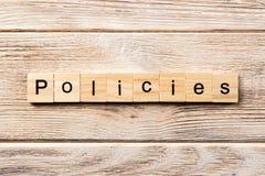 Las políticas redactan escrito en el bloque de madera texto en la tabla, concepto de las políticas imagenes de archivo
