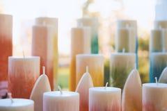 Las porciones de colocar velas coloridas con las mechas se encendieron por luz del sol Imagen de archivo libre de regalías