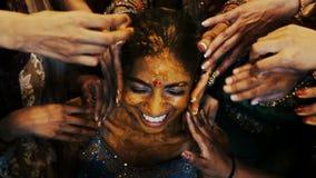 Las porciones de las manos de las mujeres frotan ligeramente la cara de la novia india cubierta con goma de la cúrcuma almacen de metraje de vídeo