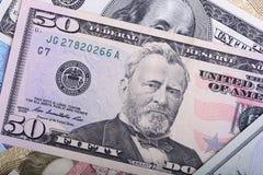 Las porciones de notas del dólar arreglaron de la manera caótica, fondo Imagenes de archivo