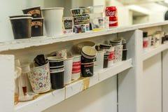 Las porciones de tazas vacías se fueron después de la prueba del café fotografía de archivo
