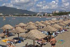 Las porciones de tener una gente del resto en la playa cultivan un huerto los mares en la ciudad de vacaciones Gelendzhik Foto de archivo
