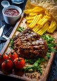Las porciones jugosas de filete de prendedero asado a la parrilla sirvieron con los tomates y Imagen de archivo libre de regalías