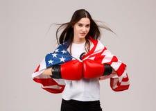 Las posiciones de una chica joven en guantes de boxeo y se cubren con una bandera americana respecto a sus hombros Fotografía de archivo