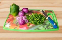 Las preparación-verduras de la comida multan tajar con el cuchillo a bordo Imágenes de archivo libres de regalías