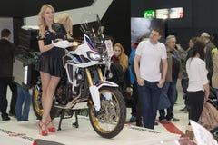 Las presentadoras hermosas presentan la motocicleta Honda CRF1000L África Twi imagenes de archivo