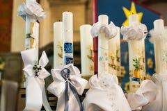 Las primeras velas ardientes de la comunión santa o de la confirmación remaron para arriba en iglesia antes de la decoración herm foto de archivo libre de regalías