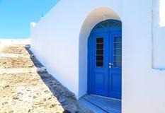 Las puertas azules brillantes, los obturadores y el blanco perfecto lavaron las paredes en las calles traseras del fira, Santorin Imagenes de archivo