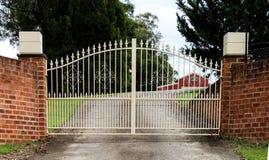 Las puertas de la entrada de la calzada del hierro labrado fijaron en cerca del ladrillo Imágenes de archivo libres de regalías