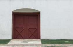 Las puertas de madera marrones viejas en las paredes blancas son cerradas fotos de archivo libres de regalías
