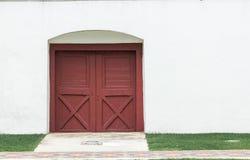 Las puertas de madera marrones viejas en las paredes blancas son cerradas fotografía de archivo