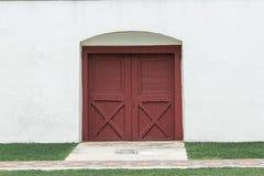 Las puertas de madera marrones viejas en las paredes blancas son cerradas fotos de archivo