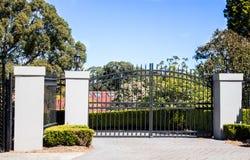 Las puertas negras de la entrada de la calzada del metal fijaron en cerca del ladrillo con los árboles del jardín en fondo fotografía de archivo libre de regalías
