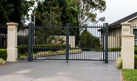 Las puertas negras de la entrada de la calzada del metal fijaron en cerca Foto de archivo