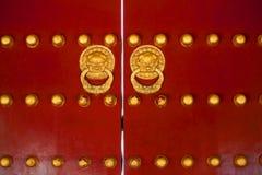 Las puertas rojas de la puerta china con el dragón de oro dirigen golpeadores Fotografía de archivo libre de regalías