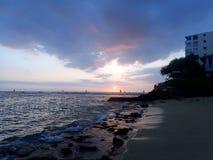 Las puestas del sol sobre Waikiki riegan como las ondas ruedan en orilla en Makalei Fotografía de archivo