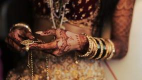 Las pulseras rojas y de oro pusieron sobre las manos de la novia india metrajes