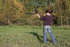 Las punterías de la muchacha de un arma Fotografía de archivo
