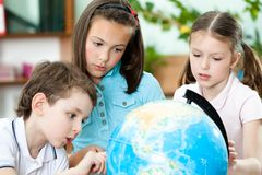 Las pupilas miran fijamente el globo de la escuela Imagen de archivo