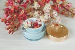 Las ramas allí blancas y rosadas del árbol de castaña con el tarro azul y de oro abierto de crema están en la tabla blanca, foco  Imagenes de archivo