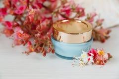 Las ramas allí blancas y rosadas del árbol de castaña con el tarro azul y de oro de crema están en la tabla blanca Fotos de archivo