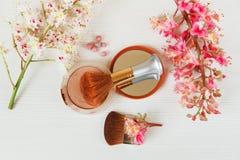 Las ramas allí blancas y rosadas del árbol de castaña, del polvo de bronce con el espejo y componen cepillos están en la tabla bl Fotos de archivo libres de regalías
