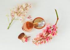 Las ramas allí blancas y rosadas del árbol de castaña, del polvo de bronce con el espejo y componen el cepillo están en la tabla  Fotos de archivo libres de regalías