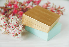 Las ramas allí blancas y rosadas del árbol de castaña, el tarro de crema y la botella de Parfum están en la tabla blanca, visión  Fotografía de archivo