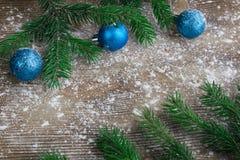 Las ramas de árbol de navidad, las bolas azules el invierno nevaron parte posterior de madera Imagenes de archivo