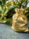 Las ramas del abeto en el fondo concreto gris con oro protagonizan La Navidad del Año Nuevo Bolso de oro con los regalos Fotos de archivo