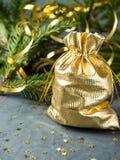 Las ramas del abeto en el fondo concreto gris con oro protagonizan La Navidad del Año Nuevo Bolso de oro con los regalos Imágenes de archivo libres de regalías
