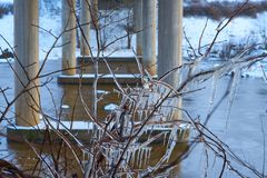 Las ramas heladas se cierran para arriba con las columnas del puente, del río y de la nieve en un fondo imagenes de archivo