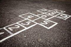 Las rayuelas cortejan con números a partir de la 1 a 10 exhaustos en el asfalto Foto de archivo libre de regalías