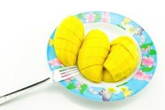 Las rebanadas amarillas del mango pusieron en una placa, fondo blanco Foto de archivo libre de regalías
