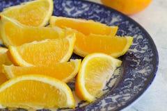 Las rebanadas anaranjadas se cierran para arriba en la placa azul y blanca Fotografía de archivo libre de regalías