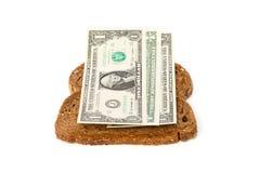 Las rebanadas de pan con los billetes de banco del dólar intercalan el relleno Imagenes de archivo