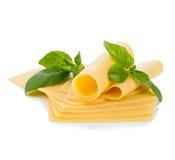 Las rebanadas de queso con albahaca fresca dejan el primer aislado en un fondo blanco Foto de archivo