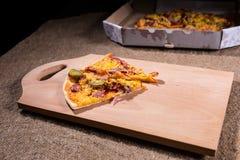 Las rebanadas de sacan la pizza en tabla de cortar de madera Fotografía de archivo libre de regalías