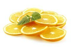 Las rebanadas de una naranja adornada con la menta de limón. Foto de archivo libre de regalías
